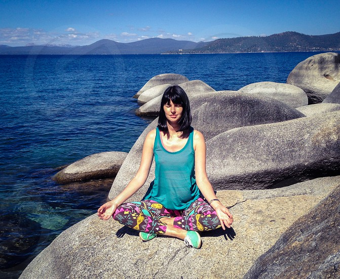 Attractive young woman in lotus pose at the Lake Tahoe. photo