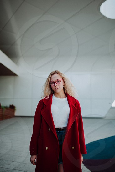 Young blonde girl posing in the modern area wearing glasses and red cloak photo