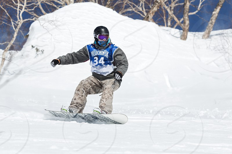 "KAMCHATKA RUSSIA - MARCH 9 2014: Snowboarder rides steep mountains. Competitions freeride skiers and snowboarders ""Kamchatka Freeride Open Cup"". Russia Far East Kamchatka Peninsula. photo"