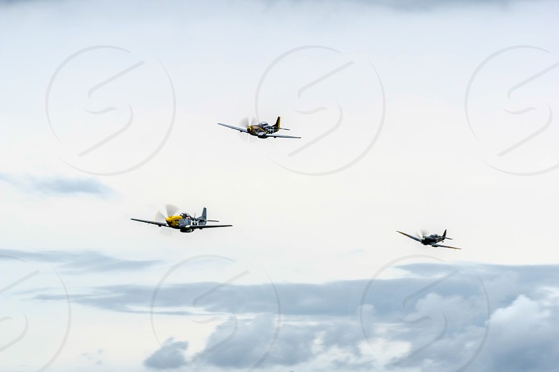 North American P-51D Mustangs and a Spitfire flying over Shoreham airfield photo