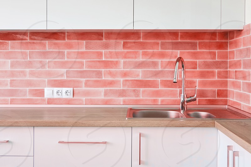 Clean interior design of modern kitchen with built-in kitchen appliances in a trend color of the year 2019 Living Coral Pantone. photo