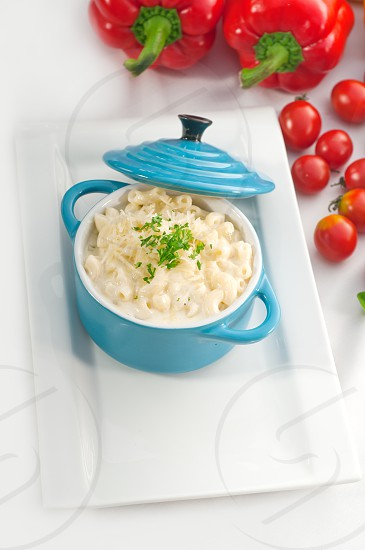 macaroni and cheesekids favourite dish  on a blue little childish clay pot with vegetables on backgroundMORE DELICIOUS FOOD ON PORTFOLIO photo