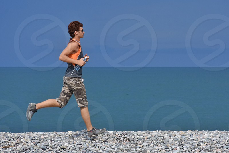 man in blue and orange tank top and brown and green camouflage shorts running on the rocky field under blue clear sky photo
