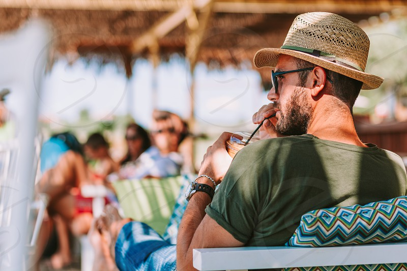 Young man drinking ice coffee in a beach bar photo