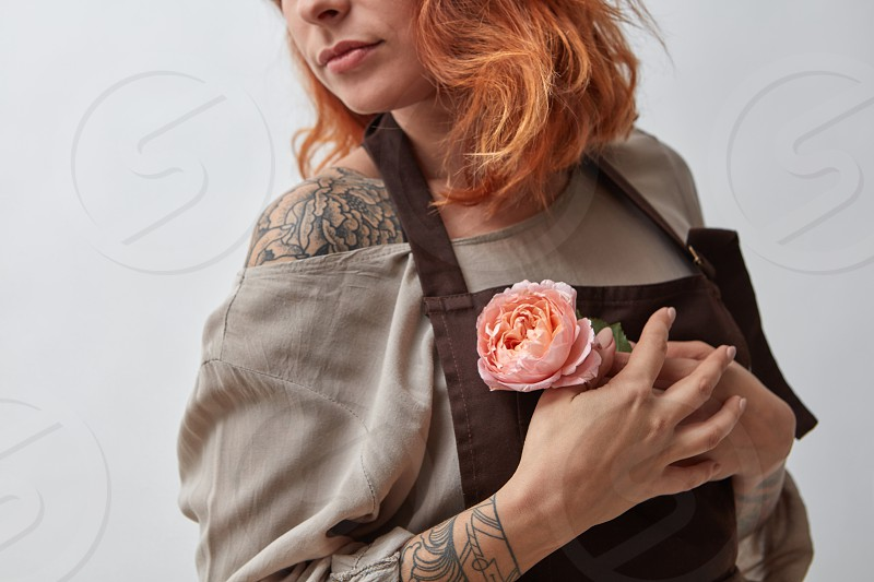 Red-haired girl with a tattoo holds in her hand a pink flower of a Ranunculus on a gray background. Mother's Day Valentine's Day photo