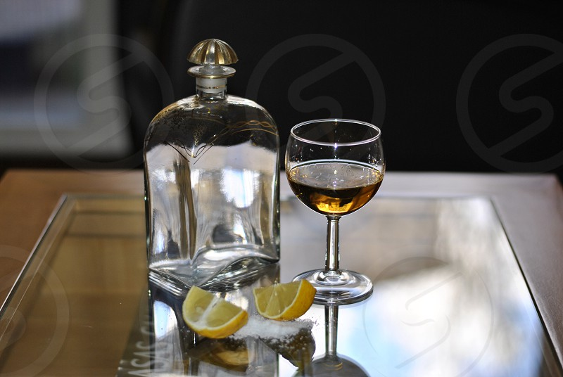 glass of liquor on table with slices of lemon and salt photo