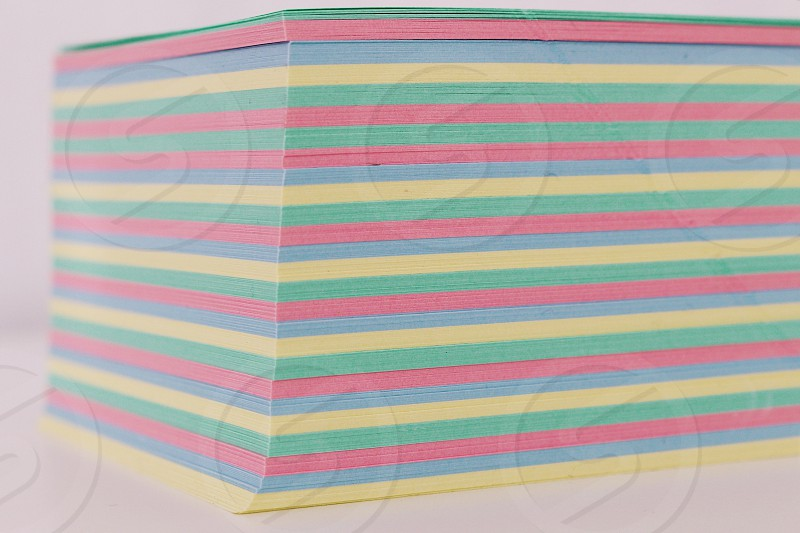 yellow pink and blue stripe notepad papers on white table photo