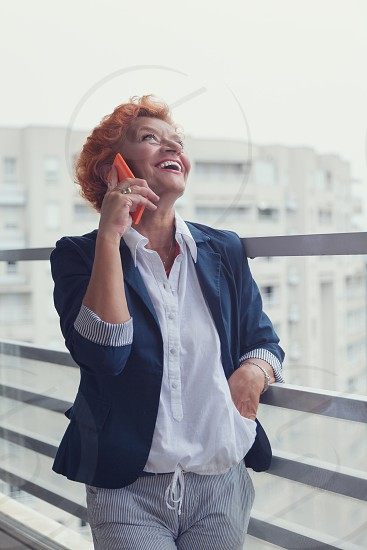Mature woman talking on a smartphone on the balcony photo