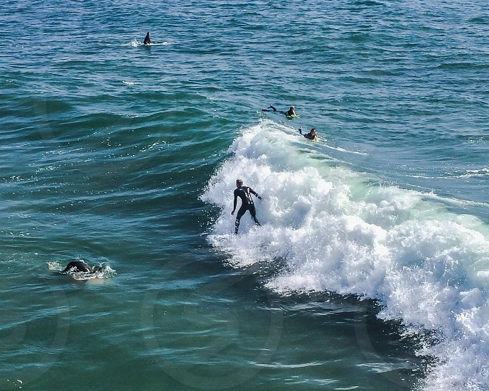 people surfing on body of water photo
