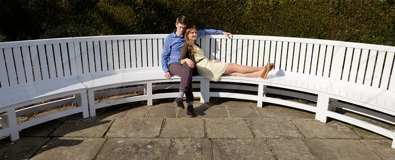 young couple looking relaxed sitting on a white long wooden garden bench in the sunshine he is wearing a blue shirt and great trousers and she is wearing a yellow dress with a brown cardigan photo