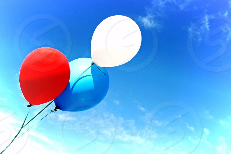 Balloons fly high in a blue sky photo