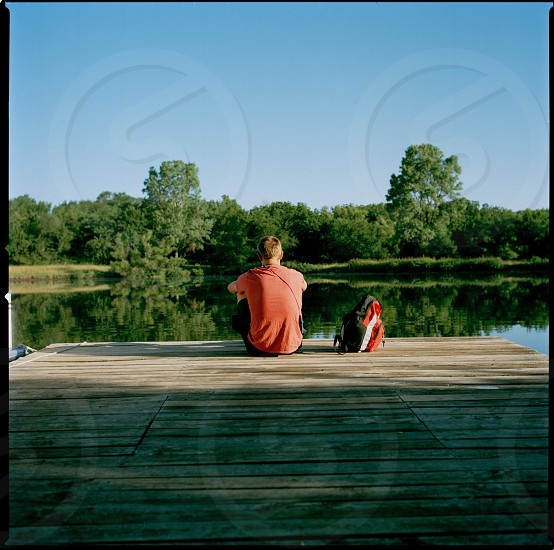 man sitting on dock with backpack photo