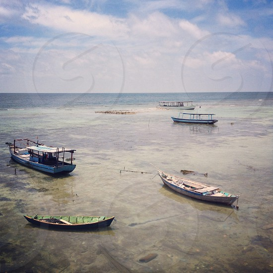 five canoes on body of water under white cloudy sky photo