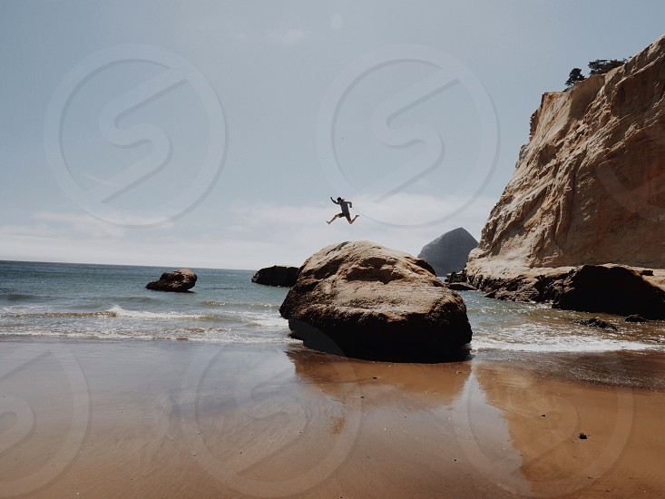 man jumping on sea photo