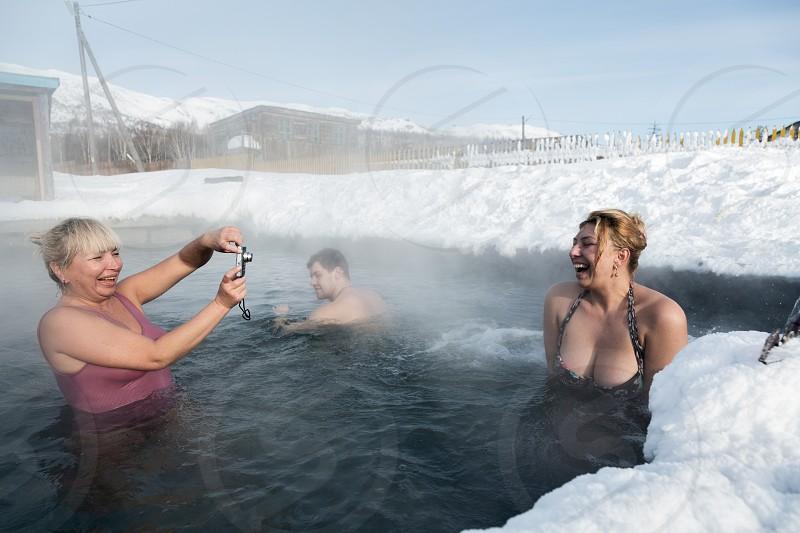 KAMCHATKA PENINSULA RUSSIA - FEB 02 2013: Two joyful women photographed while swimming in geothermal spa in hot spring pool in winter. Eurasia Russian Far East Kamchatsky Krai Anavgay Village. photo