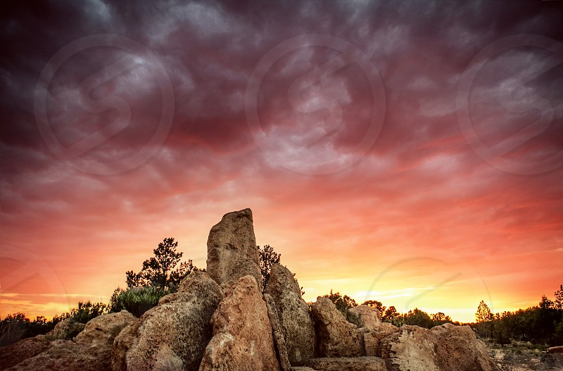 Arizona sky on fire from white to yellow orange red and violet over a red/brown rock. photo