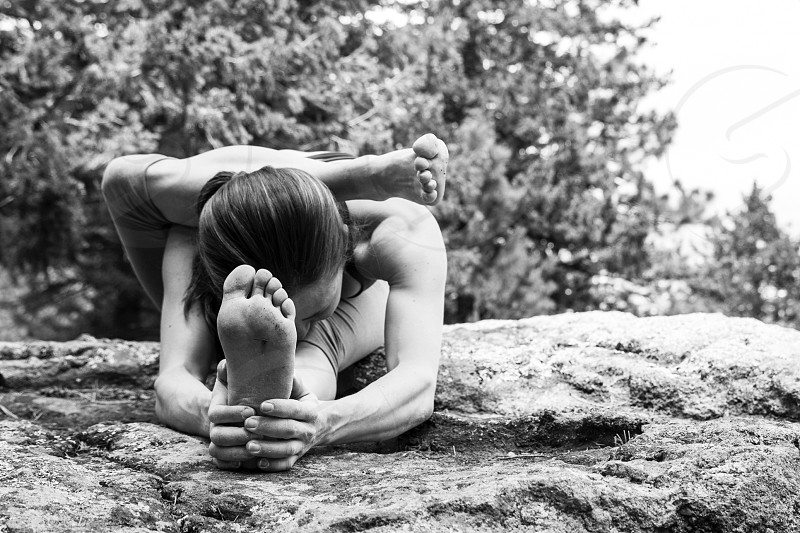 Young and flexible female practices yoga on the rocks of Boulder Colorado photo