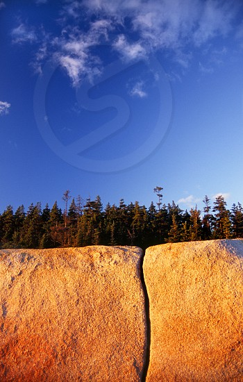 Spruce trees atop a bold orange granite cliff with a single crack in it and some wispy clouds. photo