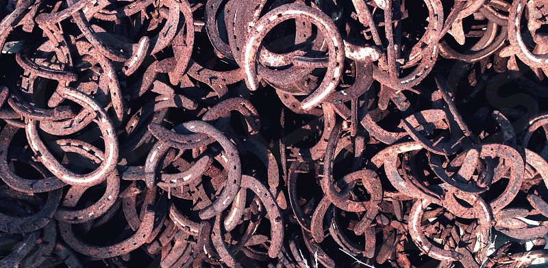 brown metal horse shoes piled during daytime photo