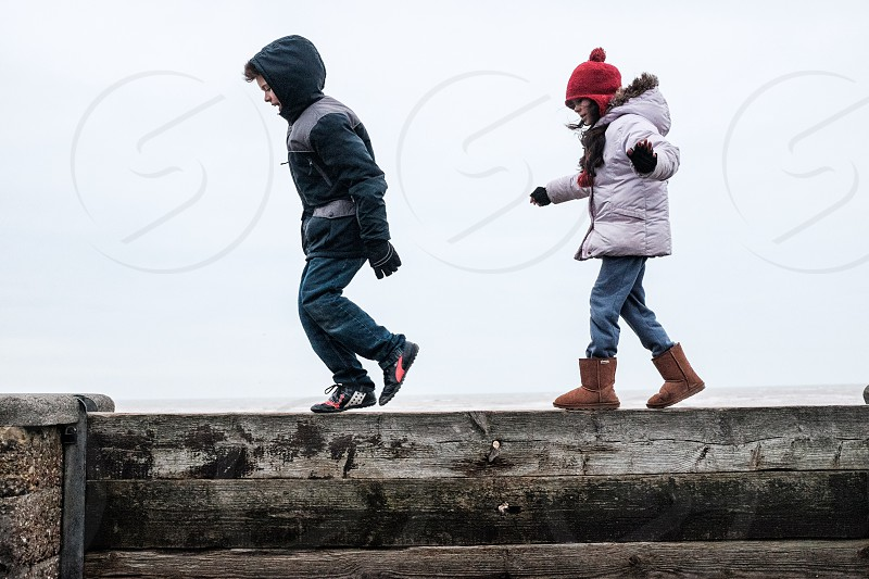 Two Kids dressed in winter clothes running on a wooden barrier between sea wall photo