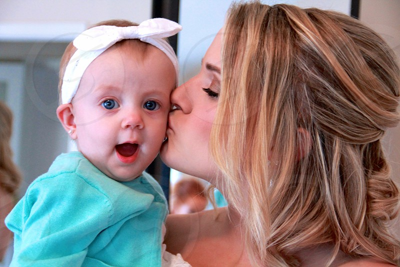 woman in gown kissing baby in teal cardigan and white bow headband photo