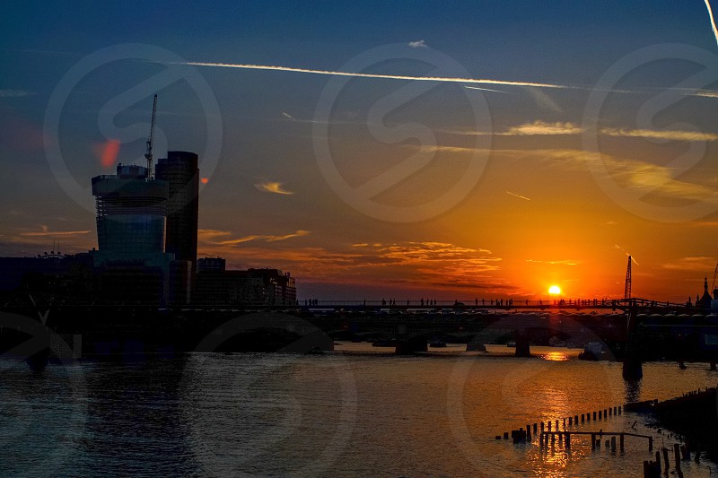 People crossing the millennium bridge in London at sunset photo