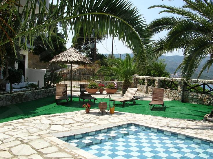 Teal summer pool patio sun loungers photo
