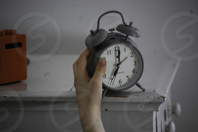 Student waking up with alarm clock on the bedside table. photo