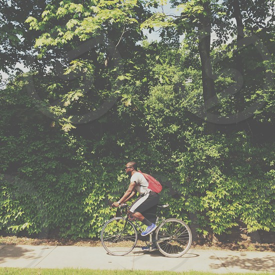man in white shirt and black shorts with red backpack riding on bicycle photo