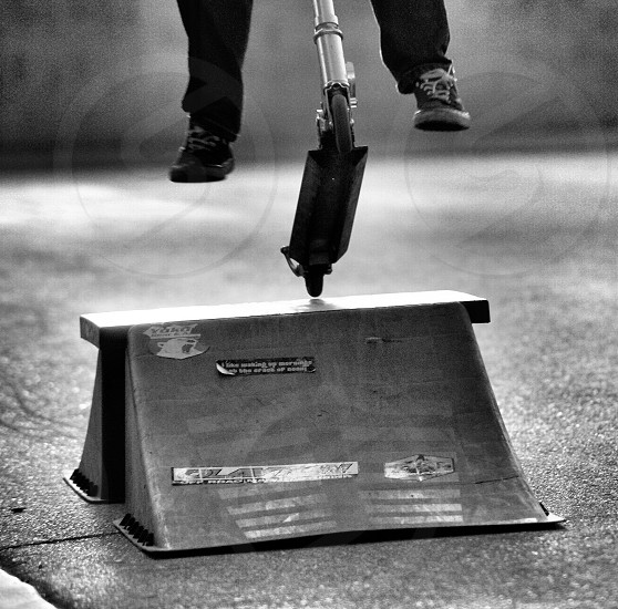 Boy jumping his scooter on a ramp in the street as a hobby or past time photo
