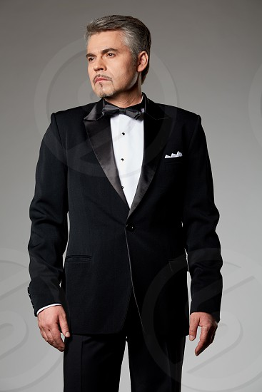 man in black blazer black pants and black bow with a white inner shirt photo