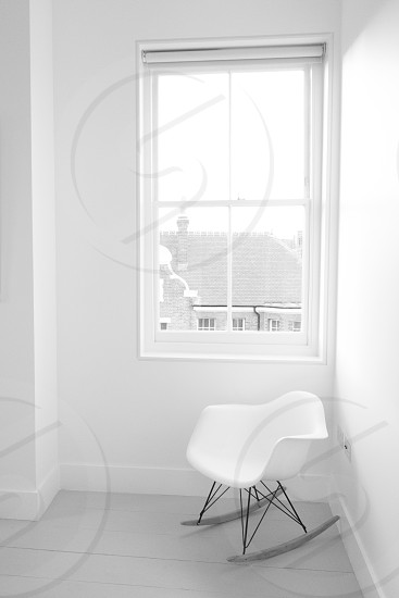 white plastic accent chair by the window photo