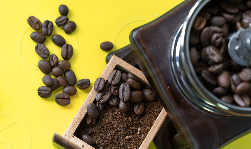 close up selective coffee beans and grinded coffee bean in vintage wooden coffee grinder on yellow background photo