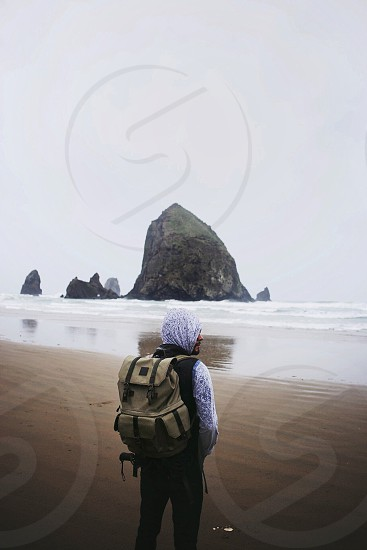 figure beige backpack white hood looking out at body of water on sand photo