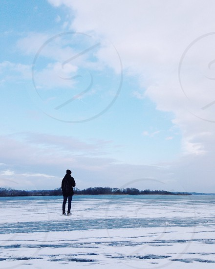 person in black coat standing on snow field under cloudy sky during daytime photo