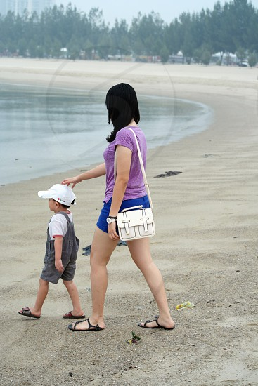 black haired woman in purple shirt standing behind child wearing white baseball cap on gray beach along body of water during daytime photo