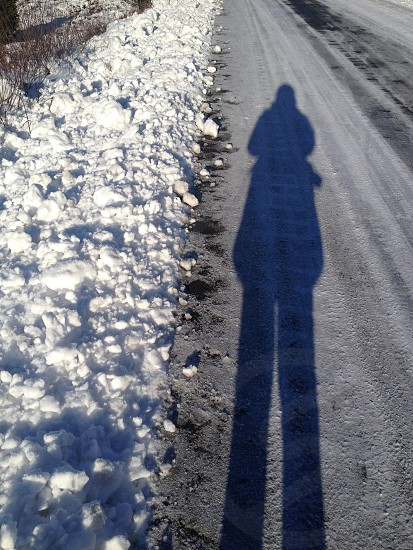 person shadow on dirt pathway passing through snow covered sidewalk photo