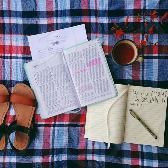 black sandals near open book besides ceramic mug with brown liquid photo