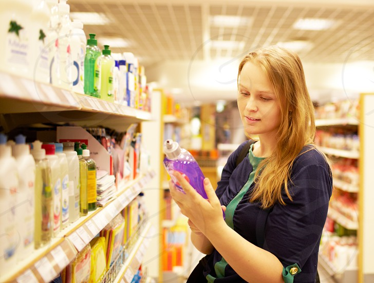 Young blonde woman is reading inscription on the cleaner bottle in the supermarket photo