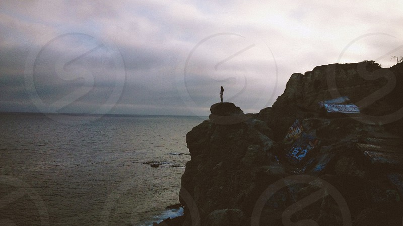 man on a cliff sihouette photo