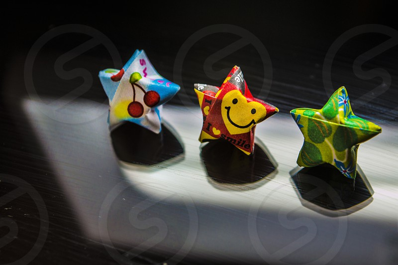 Three little colorful origami wishing stars (aka lucky stars) perched upright in a small spotlight. photo