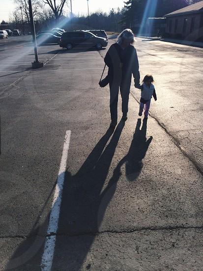 woman in black jacket walking on street photo