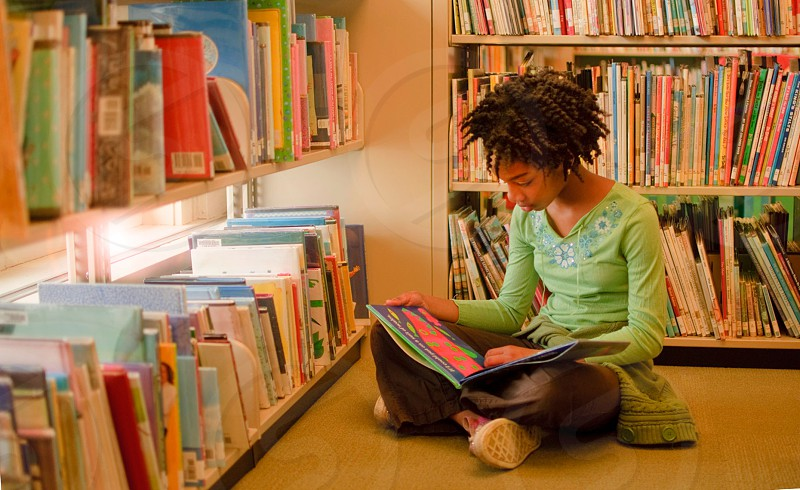 girl in green long sleeve shirt reading book in library photo