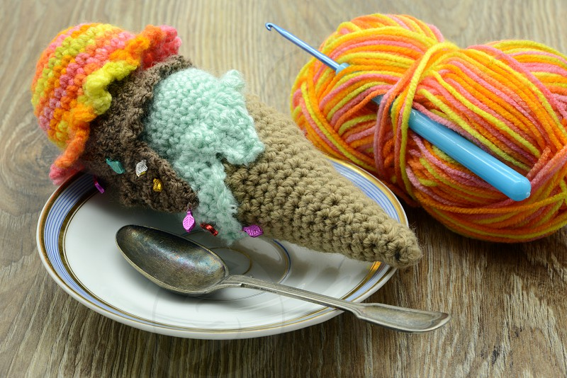 crochet ice cream cone with wool ball and crochet hook on table background photo