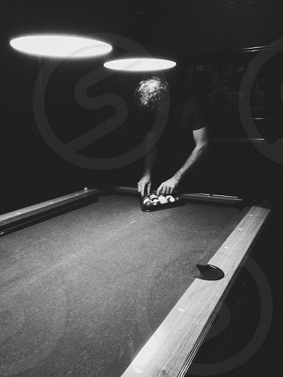 man arranging billiard ball photo