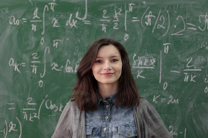 Smart pretty girl in college classroom on background of green chalkboard with high math formulas. Higher education concept. photo