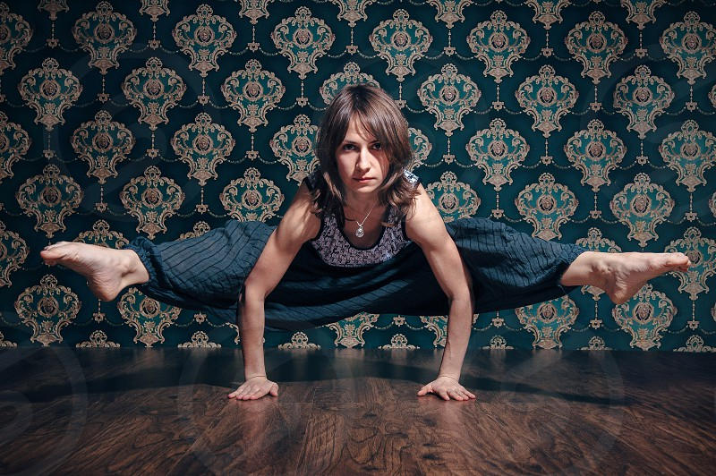Young woman doing yoga in photostudio. Pattern wallpapers background and contrast lightning photo