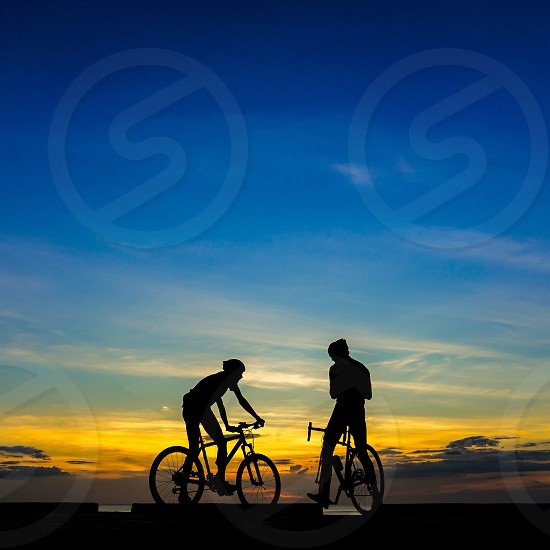 Two Cyclists with their bicycles at the beach sunset scene. photo