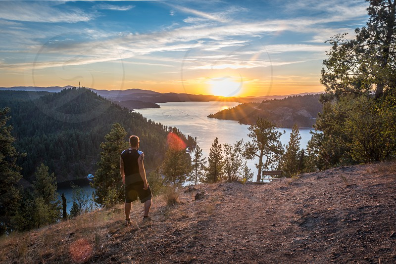 man wearing black sleeveless shirt standing near mountain cliff looking on sunset photo