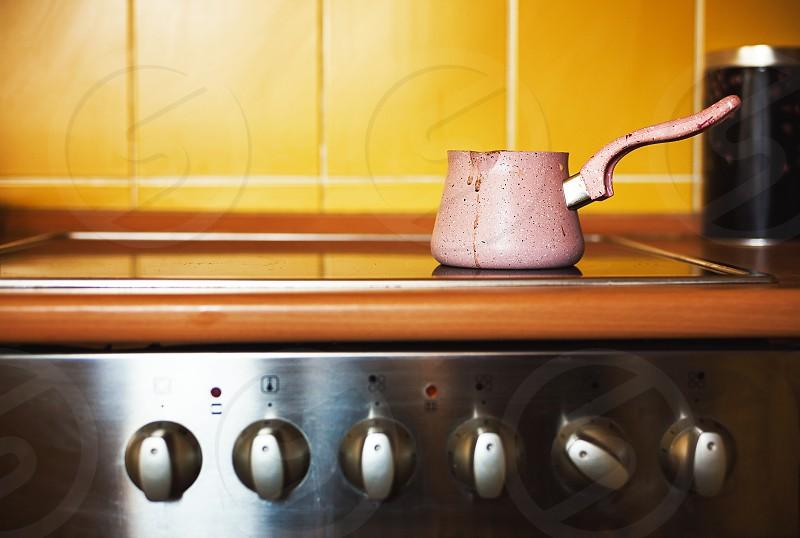 One coffee pot on kitchen stove ordinary lifestyle scene.  photo
